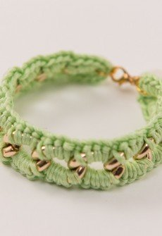 Handmade knitted bracelet from cotton yarn in peanut color and gold colored chain